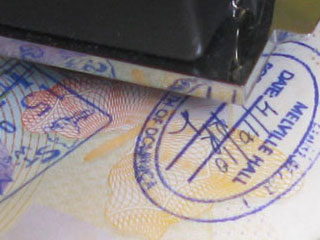 A Stamp Being Placed on the Page of a Passport